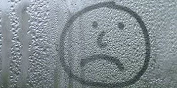 A sad face drawn on the condensation in a misty unit